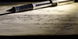 A pen laid across paper with cursive writing on it