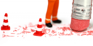 A pencil eraser flanked by mini pylons and construction workers removing a mistake